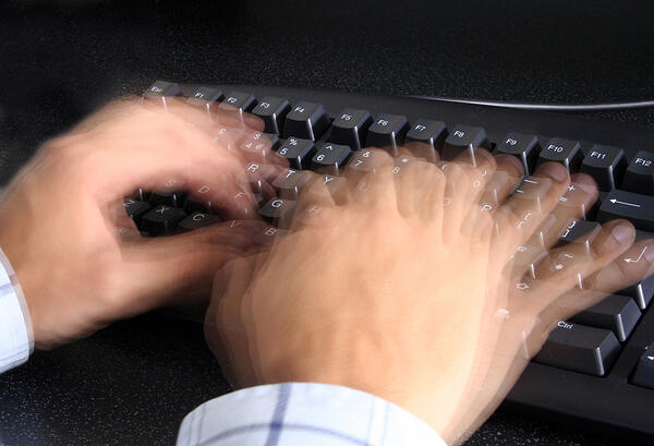 person typing incredibly fast on a keyboard
